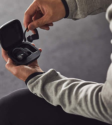someone grabbing from its case the Powerbeats Pro wireless headphones